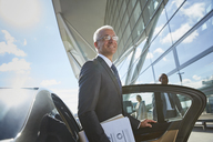 Smiling businessman arriving at airport getting out of town car - CAIF10290