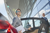 Businesswoman arriving at airport getting out of town car - CAIF10293