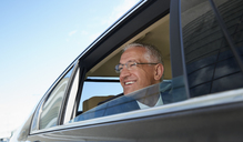 Smiling businessman looking out town car window - CAIF10299