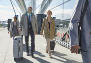Business people walking pulling suitcases outside airport - CAIF10302