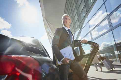 Businessman arriving at airport getting out of town car - CAIF10308