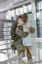 Daughter greeting hugging soldier mother at airport - CAIF10311