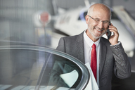 Smiling businessman talking on cell phone in airplane hangar - CAIF10314