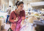 Smiling woman pointing at display case in grocery store - CAIF10347