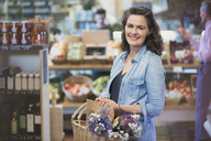 Portrait smiling woman shopping in market - CAIF10359