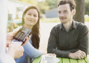 Couple watching waitress using credit card reader at outdoor cafe - CAIF10362