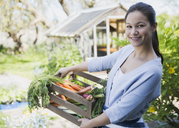 Portrait smiling woman with fresh harvested crate of vegetables in garden - CAIF10365