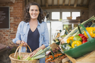 Portrait smiling woman with basket shopping for produce in market - CAIF10395