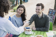 Waitress handing credit card reader to couple at outdoor cafe - CAIF10410