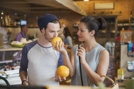 Couple smelling grapefruits in market - CAIF10425