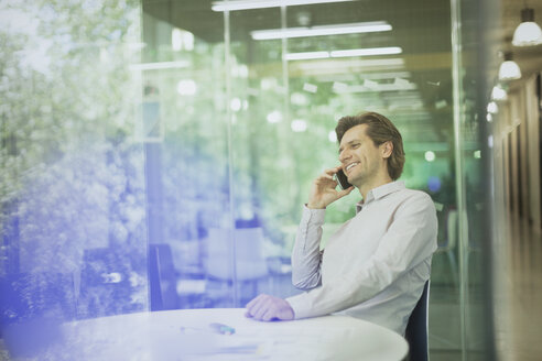 Smiling businessman talking on cell phone in conference room - CAIF10431