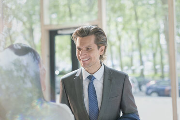 Smiling businessman talking to businesswoman in lobby - CAIF10440