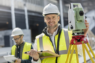 Portrait smiling male engineer using theodolite at construction site - CAIF10446