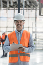 Portrait confident male engineer with clipboard at construction site - CAIF10449