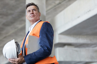 Serious businessman with hard-hat at construction site - CAIF10467