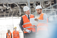 Male engineers with blueprints and clipboard discussing paperwork at construction site - CAIF10470