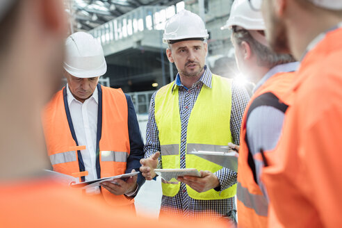 Male foreman, engineers and construction workers meeting at construction site - CAIF10473