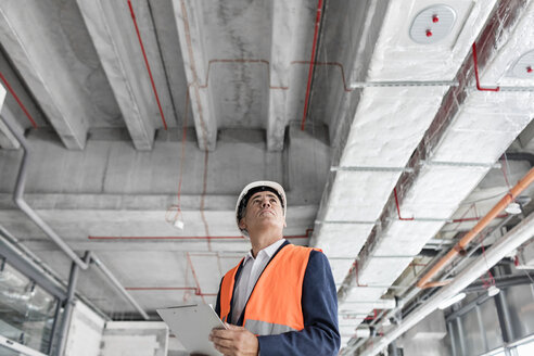 Foreman with clipboard looking up at construction site - CAIF10476