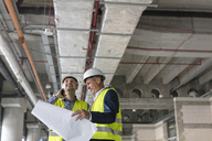 Male engineers with flashlight and blueprints at construction site - CAIF10479