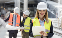 Portrait smiling female engineer with clipboard at construction site - CAIF10485