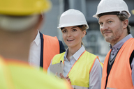 Smiling engineers meeting at construction site - CAIF10494