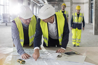 Male engineers discussing blueprints at construction site - CAIF10497