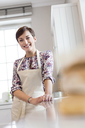 Portrait smiling brunette woman in apron in kitchen - CAIF10512