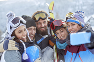 Smiling skier friends taking selfie with camera phone - CAIF10536