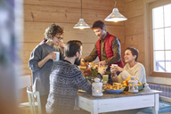 Friends eating and talking at cabin table - CAIF10548