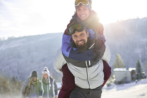 Portrait playful couple piggybacking in sunny, snowy field - CAIF10572