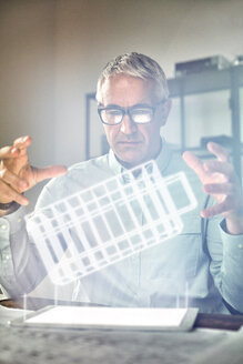 Male architect performing telekinesis, hovering futuristic glowing plastic model - CAIF10587