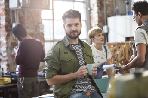 Portrait confident young male designer drinking coffee in workshop - CAIF10593