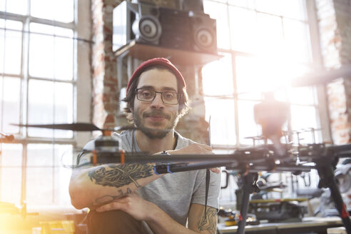 Portrait confident male designer with tattoos working on drone in workshop - CAIF10614