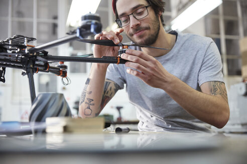 Male designer with tattoos assembling drone in workshop - CAIF10623
