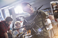 Male designer assembling drone in workshop - CAIF10629