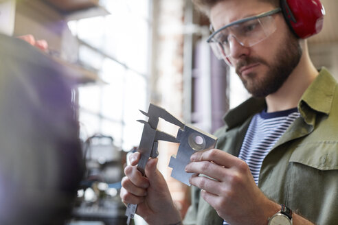 Male designer using calipers in workshop - CAIF10638