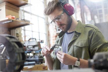 Male designer using caliper in workshop - CAIF10647
