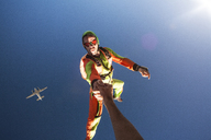 Man holding friends hand while BASE jumping in sky - CAVF05197