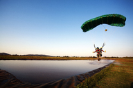 Man parasailing over lake against clear sky - CAVF05215