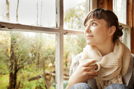 Woman looking away while sitting by window at home - CAVF05248