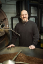 Portrait of man standing by coffee roaster at industry - CAVF05290