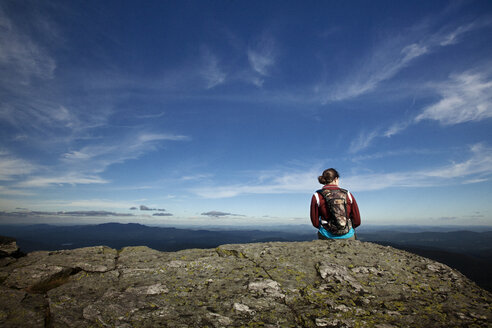 Rear view of woman with backpack sitting on cliff against sky - CAVF05509