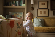 Curious baby boy looking away while standing by sofa at home - CAVF05518