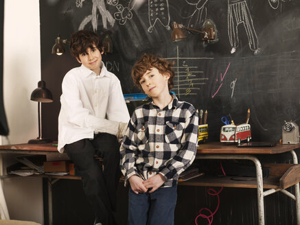 Portrait of brothers against blackboard at home - CAVF05554