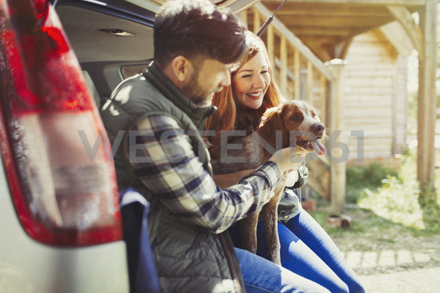 Couple petting pet dog at back of car - CAIF10695