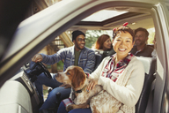 Portrait smiling woman with dog on lap in car with friends - CAIF10704