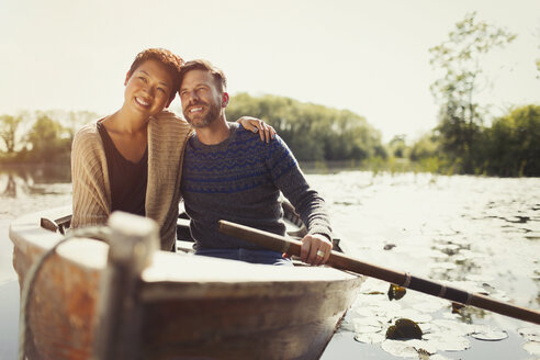 Portrait hugging couple canoeing on sunny lake - CAIF10707