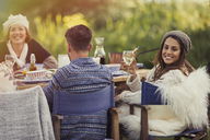 Portrait smiling woman drinking wine at garden lunch table - CAIF10713
