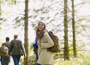 Enthusiastic woman with backpack hiking in sunny woods - CAIF10719