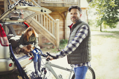Portrait smiling man with mountain bike near car behind cabin - CAIF10734